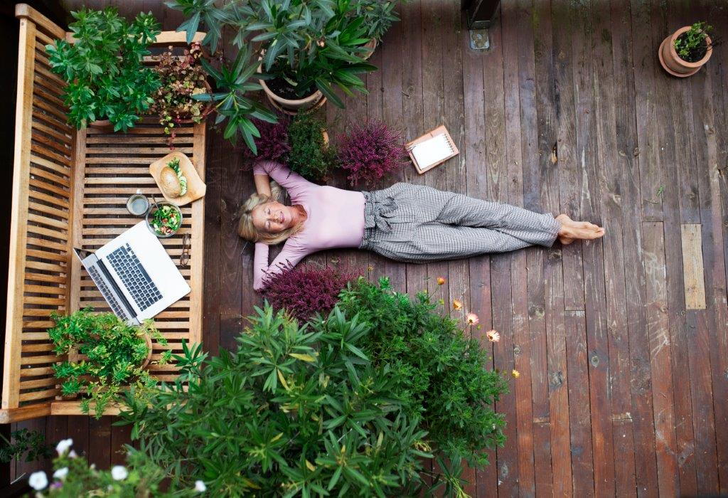 woman laying on a deck outside with plants